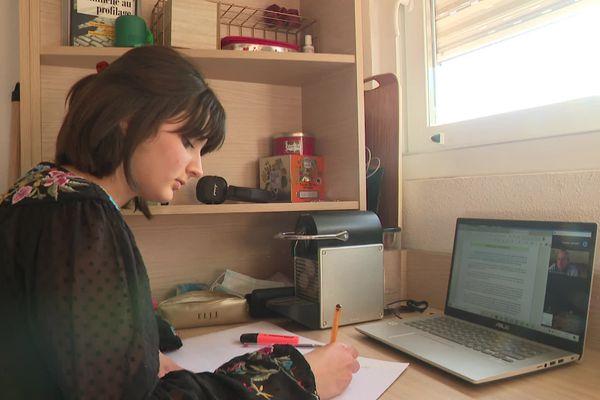 Camille Erhart assiste à un cours de droit en visioconférence.