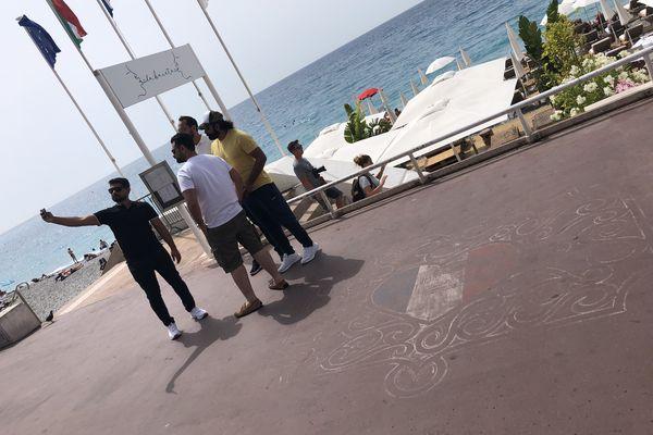 Des touristes prennent un autoportrait à côté d'un dessin réalisé en mémoire des victimes de l'attentat de Nice.